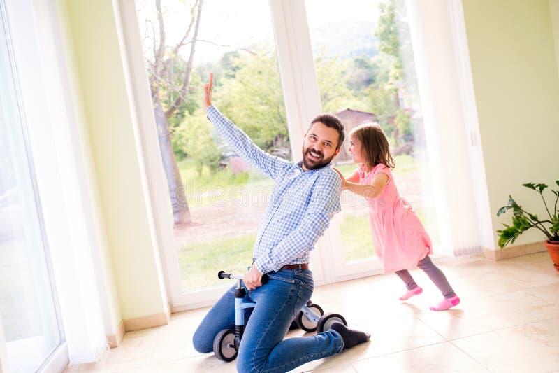 Παιχνίδι πατέρων και κορών μαζί, που οδηγά ένα ποδήλατο στο εσωτερικό στοκ εικόνα