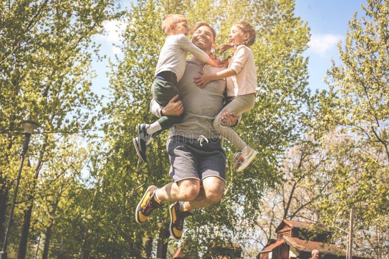 Παιχνίδι πατέρων με τα παιδιά του ` s στο λιβάδι Fathe στοκ εικόνες