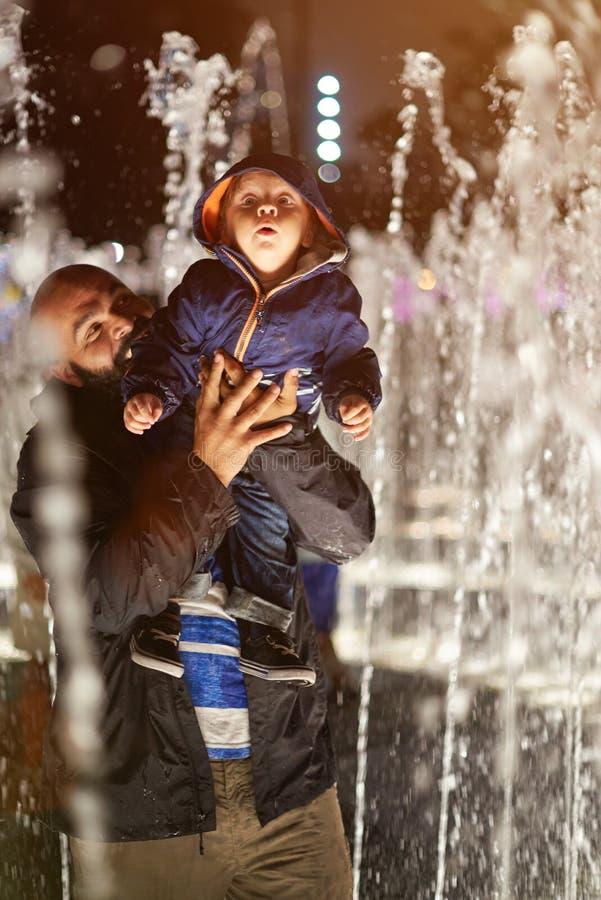 Παιχνίδι πατέρων με το παιδί στην πηγή στοκ φωτογραφίες