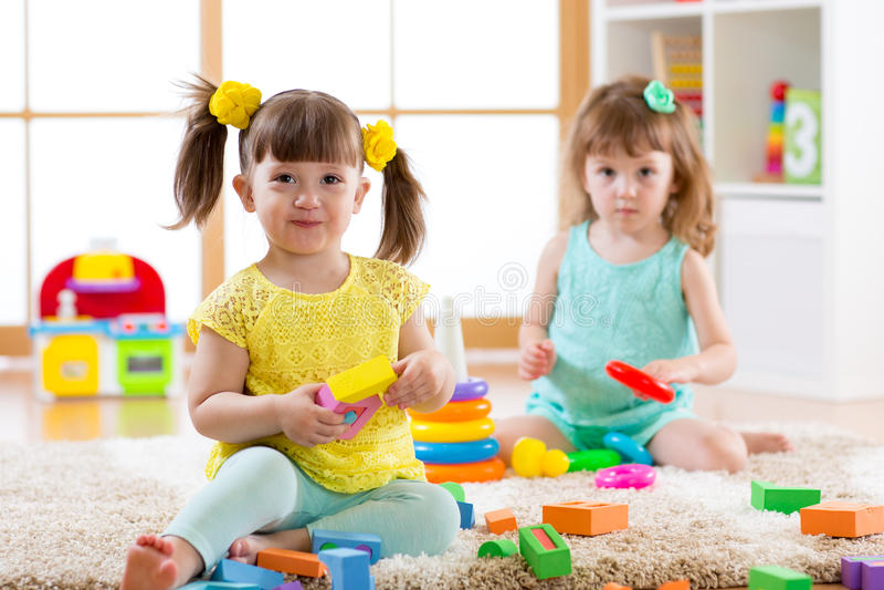Παιδάκια που παίζουν με τα ζωηρόχρωμα παιχνίδια στο πάτωμα στο σπίτι ή τον παιδικό σταθμό Εκπαιδευτικά παιχνίδια για τα παιδιά στοκ φωτογραφία