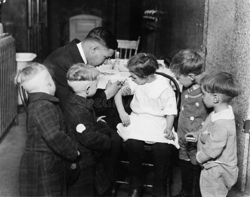 Παιδίατρος που ανοσοποιεί ένα μικρό κορίτσι ενώ άλλα παιδιά προσέχουν (όλα τα πρόσωπα που απεικονίζονται δεν ζουν περισσότερο και στοκ φωτογραφία με δικαίωμα ελεύθερης χρήσης