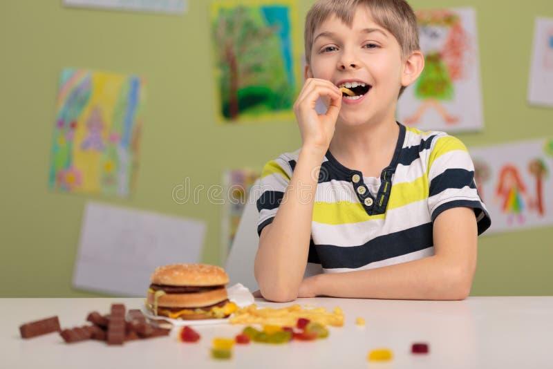 Παιδί και ανθυγειινά πρόχειρα φαγητά στοκ εικόνες