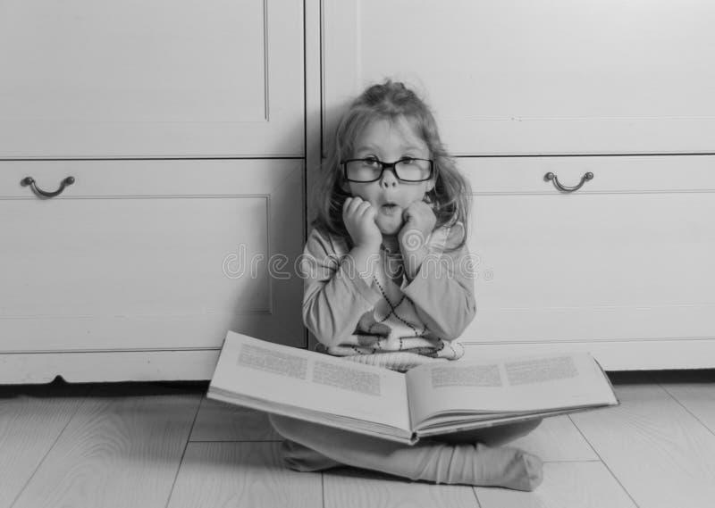 Παιδί κοριτσιών με ένα βιβλίο με τα γυαλιά που κάθονται στο πάτωμα, γραπτό στοκ φωτογραφίες