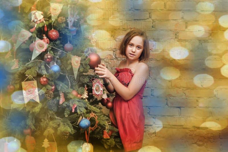 Παιδί κοριτσιών στο κόκκινο φόρεμα στο χριστουγεννιάτικο δέντρο στοκ εικόνες