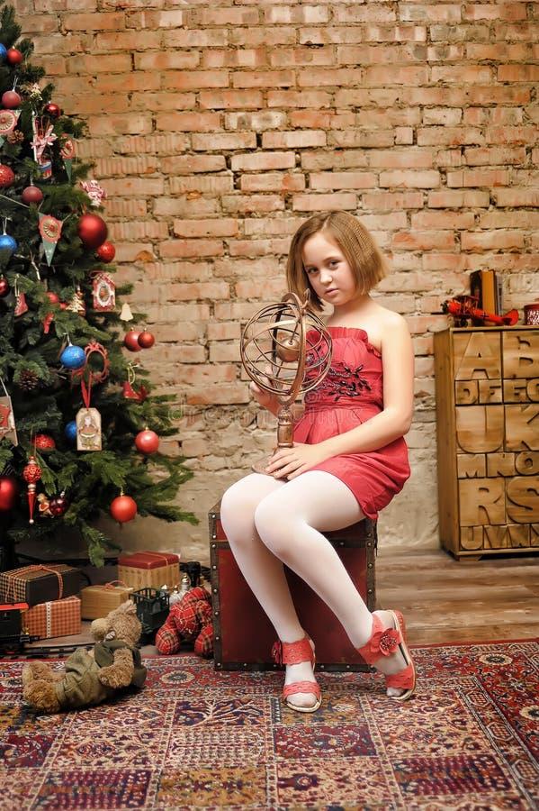 Παιδί κοριτσιών στο κόκκινο φόρεμα στο χριστουγεννιάτικο δέντρο στοκ φωτογραφία με δικαίωμα ελεύθερης χρήσης