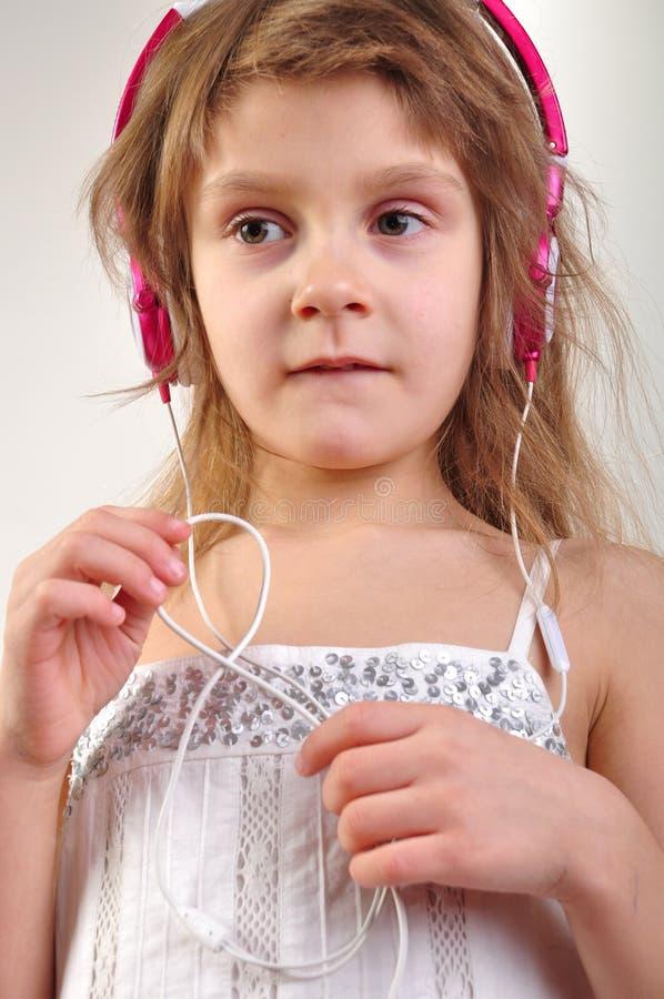 Παιδί με τα ακουστικά που ακούει τη μουσική στοκ εικόνες