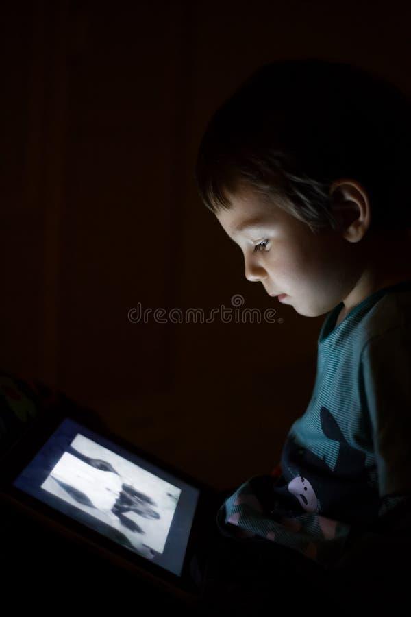 Παιδί με την ταμπλέτα στο σκοτάδι στοκ εικόνες με δικαίωμα ελεύθερης χρήσης