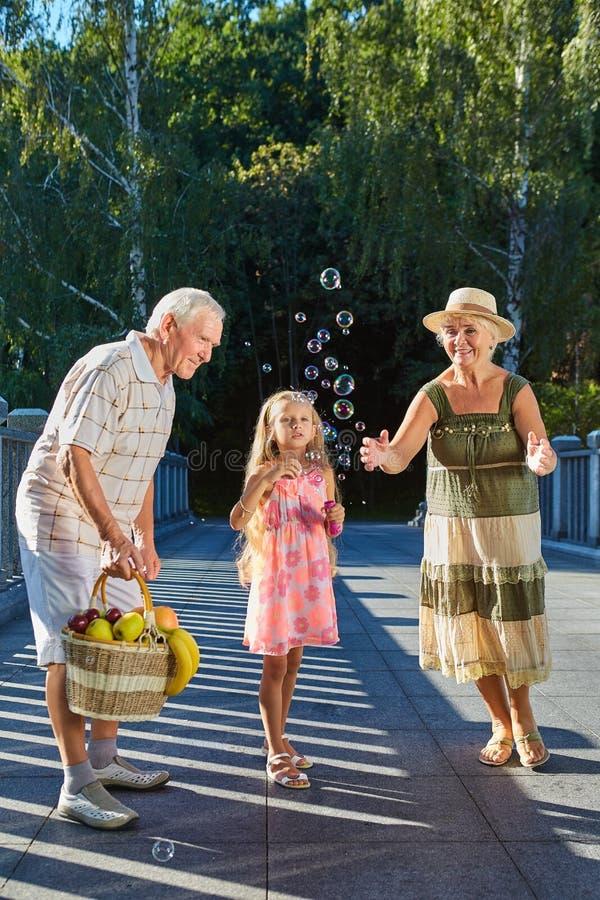 Παιδί με τον ανεμιστήρα φυσαλίδων, παππούδες και γιαγιάδες στοκ εικόνα