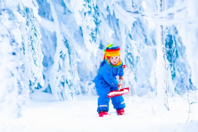 Παιδί με το φτυάρι χιονιού το χειμώνα στοκ φωτογραφία με δικαίωμα ελεύθερης χρήσης