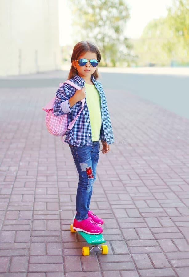 Παιδί μικρών κοριτσιών μόδας με skateboard που φορά τα γυαλιά ηλίου και το ελεγμένα πουκάμισο και το σακίδιο πλάτης στοκ εικόνες