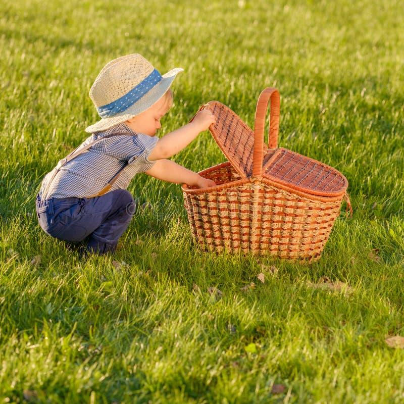 Παιδί μικρών παιδιών υπαίθρια Αγοράκι ενός έτους βρεφών που φορά το καπέλο αχύρου που κοιτάζει στο καλάθι πικ-νίκ στοκ φωτογραφίες