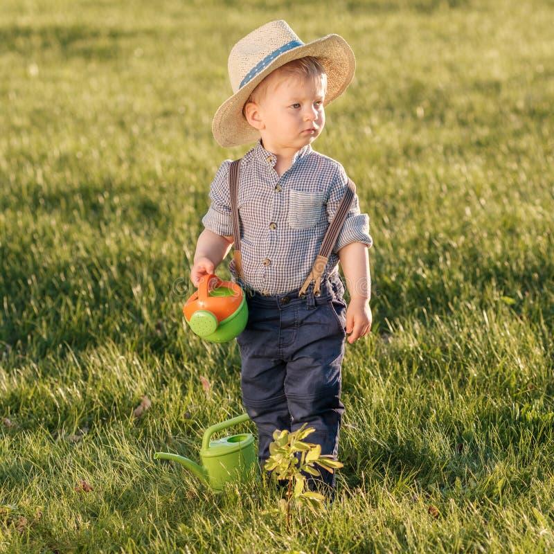 Παιδί μικρών παιδιών υπαίθρια Το αγοράκι ενός έτους βρεφών που φορά το καπέλο αχύρου που χρησιμοποιεί το πότισμα μπορεί στοκ φωτογραφία με δικαίωμα ελεύθερης χρήσης