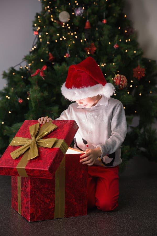 Παιδί που ανοίγει το χριστουγεννιάτικο δώρο του στοκ φωτογραφία