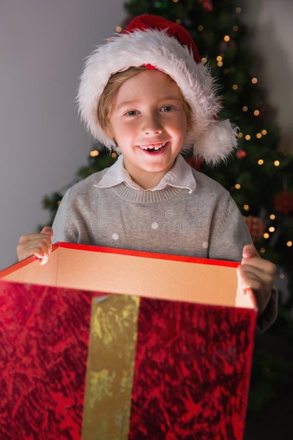 Παιδί που ανοίγει το χριστουγεννιάτικο δώρο του στοκ εικόνα με δικαίωμα ελεύθερης χρήσης