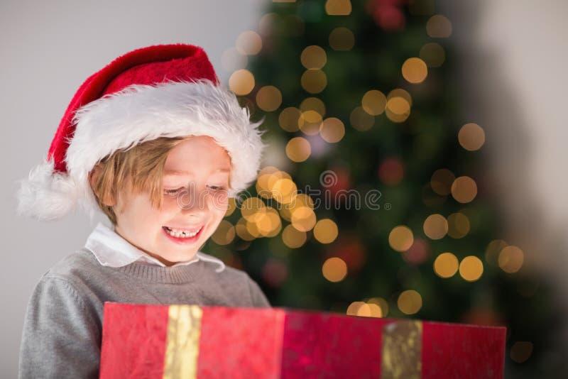 Παιδί που ανοίγει το χριστουγεννιάτικο δώρο του στοκ εικόνες