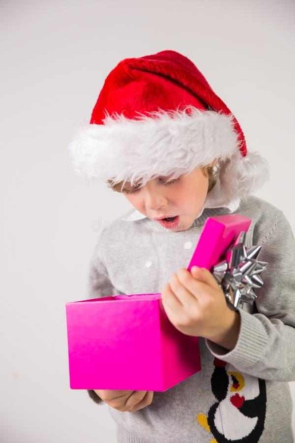 Παιδί που ανοίγει το χριστουγεννιάτικο δώρο του στοκ εικόνα