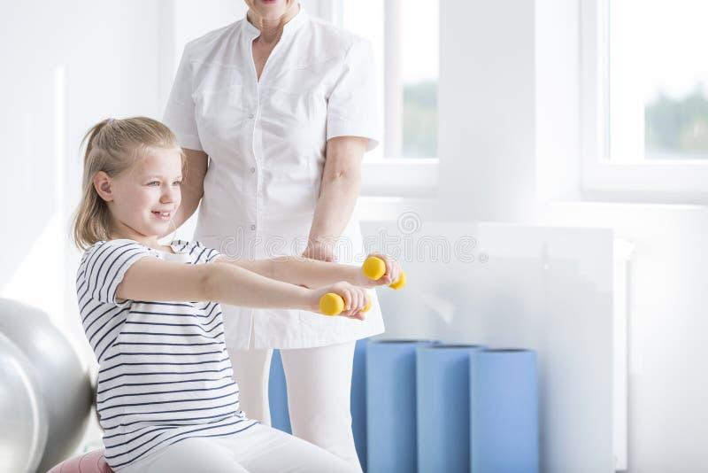 Παιδί που ασκεί με τους κίτρινους αλτήρες στοκ εικόνες