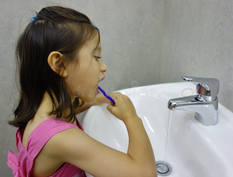 Παιδί που βουρτσίζει τα δόντια της. στοκ εικόνες