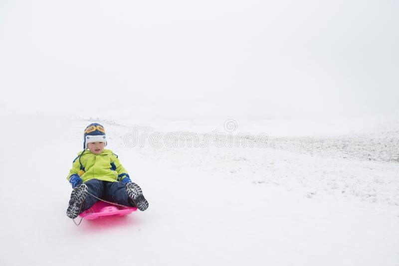 Παιδί που γλιστρά στο χιόνι στοκ φωτογραφίες με δικαίωμα ελεύθερης χρήσης