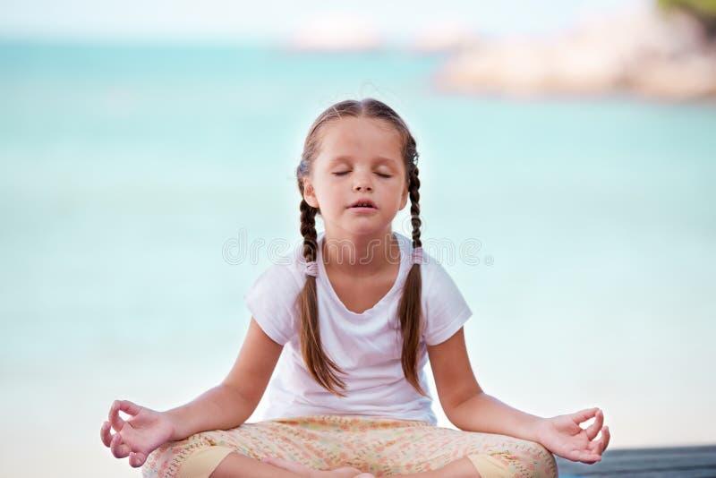 Παιδί που κάνει την άσκηση στην πλατφόρμα υπαίθρια Υγιής τρόπος ζωής το κορίτσι ανασκόπησης απομόνωσε την άσπρη γιόγκα στοκ φωτογραφία