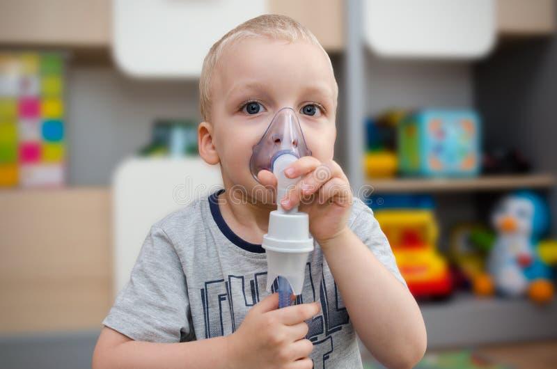 Παιδί που κάνει την εισπνοή με τη μάσκα στο πρόσωπό του στοκ εικόνα
