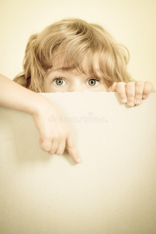 Παιδί που κοιτάζει από πίσω από το κενό εγγράφου στοκ εικόνες με δικαίωμα ελεύθερης χρήσης