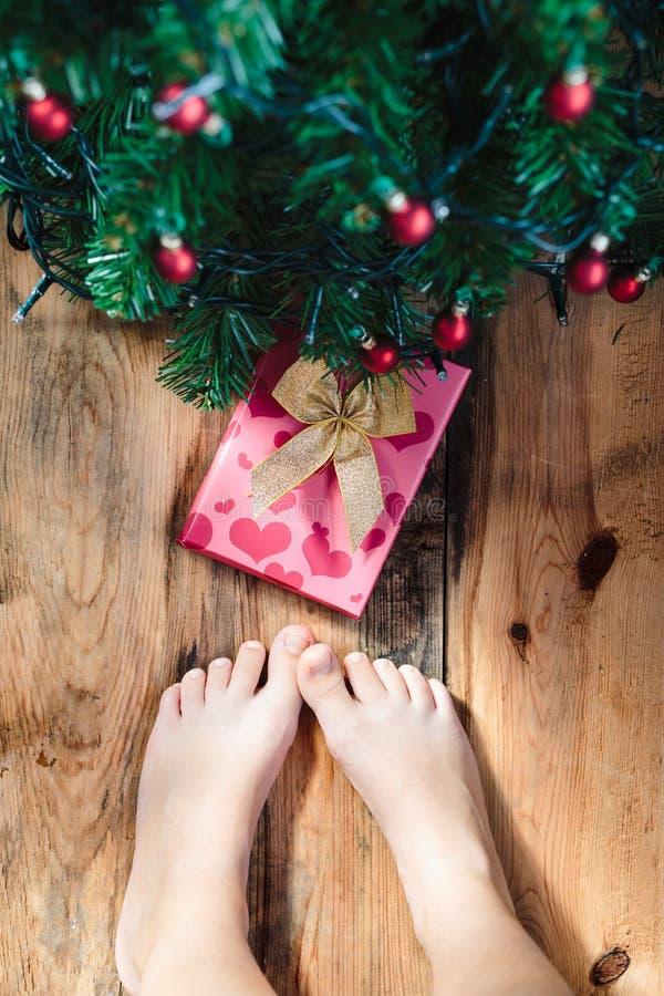 Παιδί που κοιτάζει κάτω αυτή τη στιγμή κάτω από το χριστουγεννιάτικο δέντρο στοκ φωτογραφία