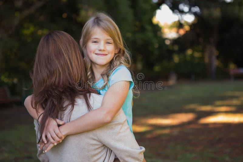 Παιδί που κοιτάζει πέρα από τον ώμο μητέρων της στοκ φωτογραφία