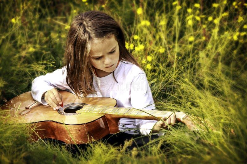 Παιδί που παίζει μια κιθάρα στοκ φωτογραφία