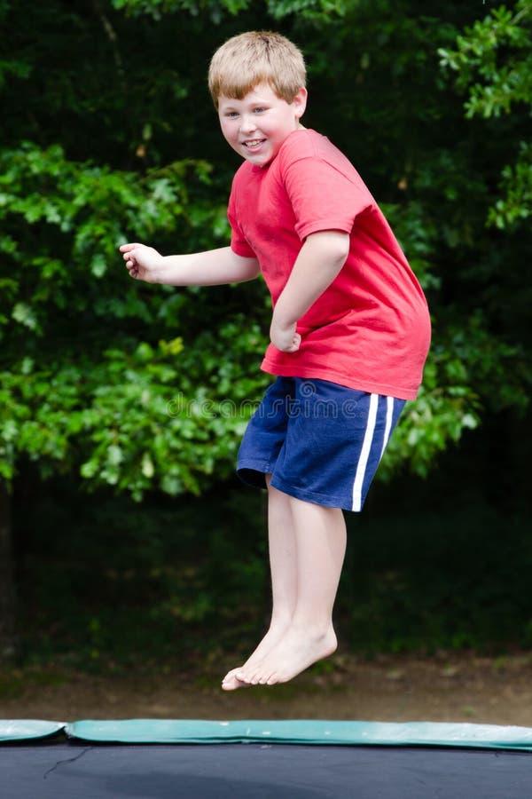Παιδί που παίζει πηδώντας στο τραμπολίνο υπαίθρια στοκ φωτογραφία