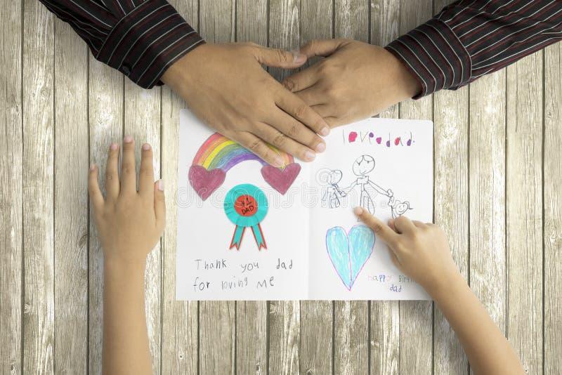Παιδί που παρουσιάζει εικόνα στον πατέρα στη ευχετήρια κάρτα στοκ φωτογραφία