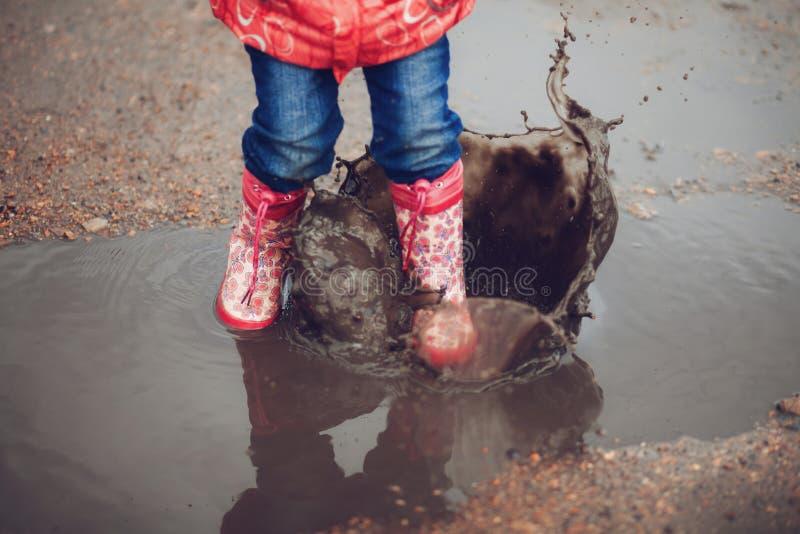 Παιδί που φορά τις ρόδινες μπότες βροχής που πηδούν σε μια λακκούβα στοκ φωτογραφία με δικαίωμα ελεύθερης χρήσης