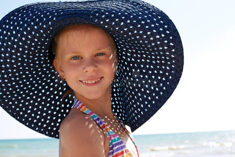 Παιδί στην μπλε χαλάρωση καπέλων στην παραλία στοκ εικόνα με δικαίωμα ελεύθερης χρήσης