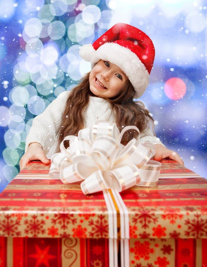 Παιδί στο καπέλο Santa με το κιβώτιο δώρων. στοκ φωτογραφίες