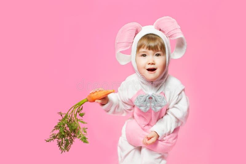 Παιδί bunny στα καρότα εκμετάλλευσης κοστουμιών λαγών. στοκ εικόνα με δικαίωμα ελεύθερης χρήσης