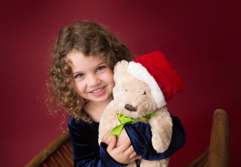 Παιδί Chirstmas με το παιχνίδι: Κόκκινο χειμερινό υπόβαθρο διακοπών στοκ φωτογραφίες