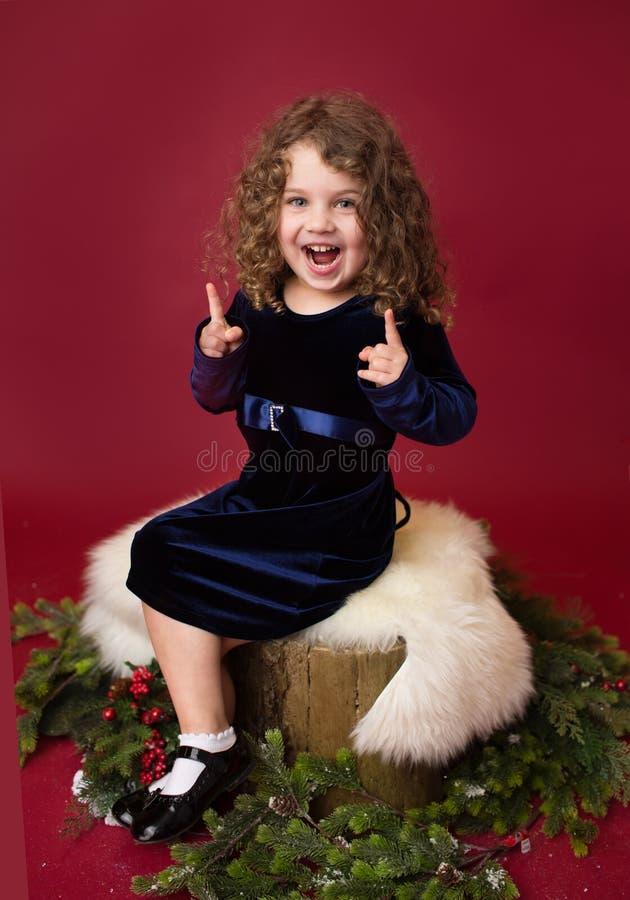 Παιδί Chirstmas που γελά και που δείχνει  Κόκκινο χειμερινό υπόβαθρο διακοπών στοκ φωτογραφία με δικαίωμα ελεύθερης χρήσης