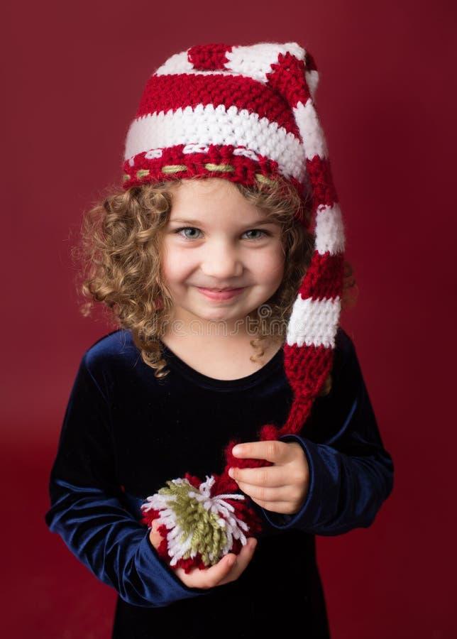 Παιδί Chirstmas που φορά το καπέλο νεραιδών Santa  Κόκκινες διακοπές χειμώνας Backgr στοκ εικόνες με δικαίωμα ελεύθερης χρήσης