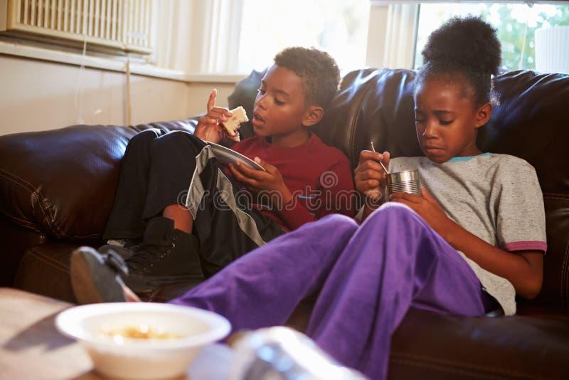Παιδιά με τη φτωχή διατροφή που τρώνε το γεύμα στον καναπέ στο σπίτι στοκ φωτογραφίες