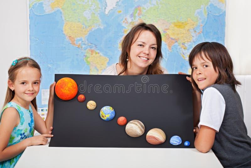 Παιδιά με το δάσκαλο επιστημών τους που παρουσιάζει πρόγραμμα-εστίασή τους στο τ στοκ φωτογραφία