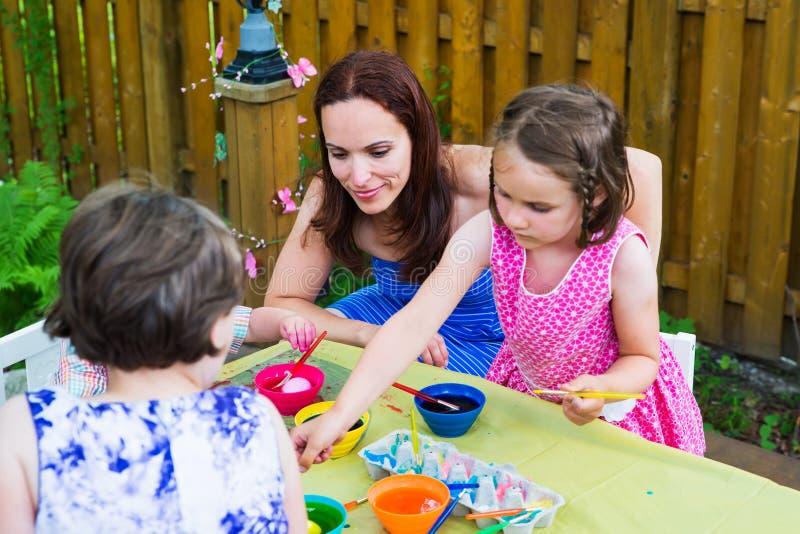 Παιδιά με Mom που βάφουν τα αυγά Πάσχας έξω στοκ φωτογραφίες