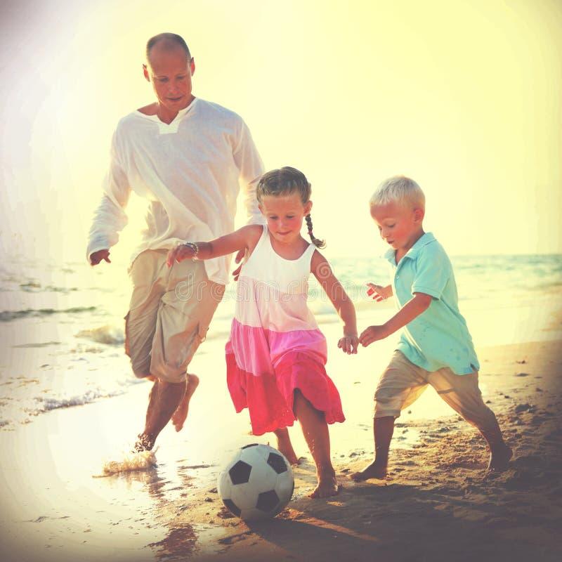 Παιδιά πατέρων που παίζουν την έννοια θερινού ελεύθερου χρόνου ποδοσφαίρου μαζί στοκ εικόνες