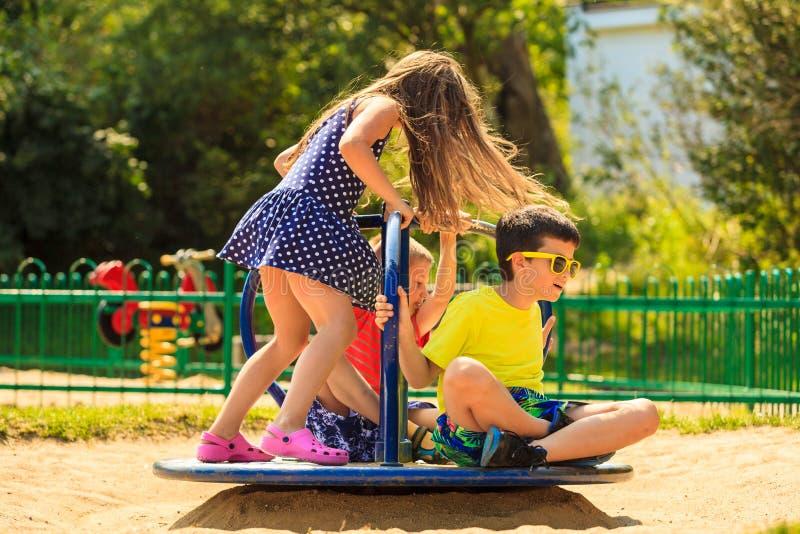 Παιδιά που έχουν τη διασκέδαση στην παιδική χαρά στοκ εικόνα