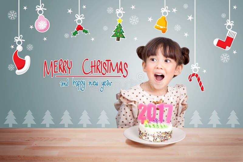 Παιδιά που έχουν τη διασκέδαση στο νέο κόμμα έτους με το κέικ και το κερί 2017 στοκ φωτογραφία