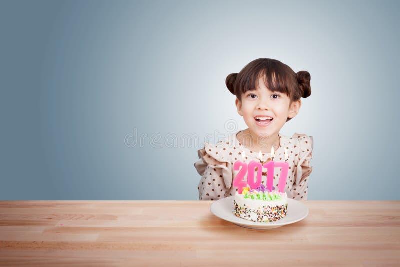 Παιδιά που έχουν τη διασκέδαση στο νέο κόμμα έτους με το κέικ και το κερί 2017 στοκ εικόνες