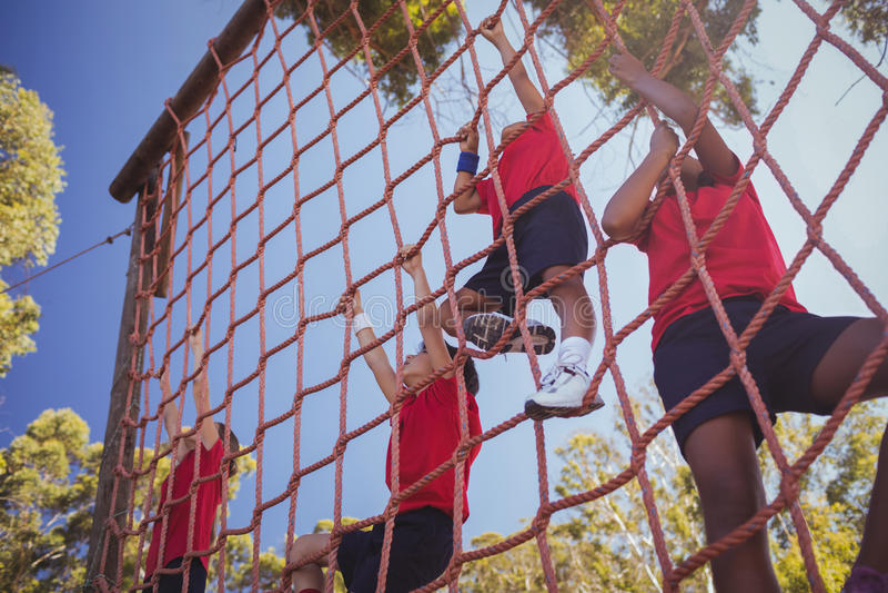 Παιδιά που αναρριχούνται σε ένα δίχτυ κατά τη διάρκεια της κατάρτισης σειράς μαθημάτων εμποδίων στοκ φωτογραφία