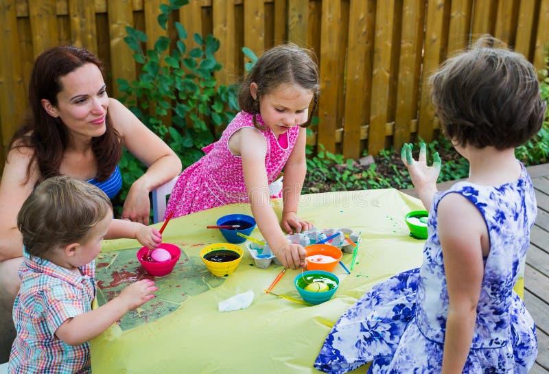 Παιδιά που βάφουν τα αυγά Πάσχας έξω στοκ φωτογραφία