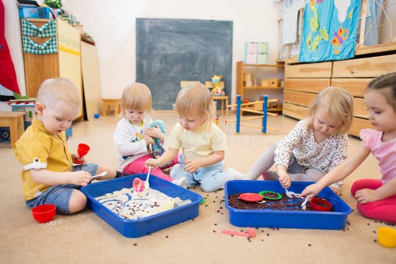 Παιδιά που βελτιώνουν τις δεξιότητες μηχανών χεριών με το ρύζι και τα φασόλια στοκ εικόνα