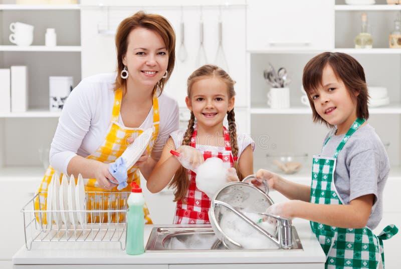 Παιδιά που βοηθούν τη μητέρα τους στην κουζίνα στοκ εικόνα