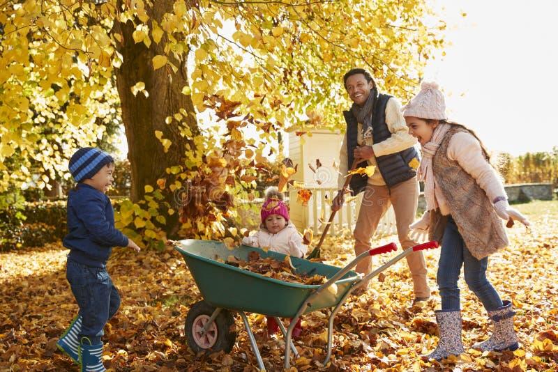 Παιδιά που βοηθούν τον πατέρα για να συλλέξει τα φύλλα φθινοπώρου στον κήπο στοκ εικόνες